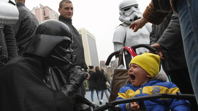 A candidate dressed as Darth Vader and representing the Internet Party of Ukraine which runs for parliament, gestures in front of a crying boy during a meeting with his supporters and voters in Kiev
